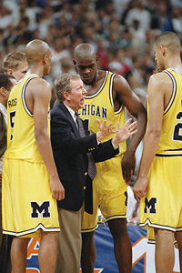 Michigan's Chris Webber, center, listens to coach Steve Fisher during the last official timeout of their Final Four championship game against North Carolina.