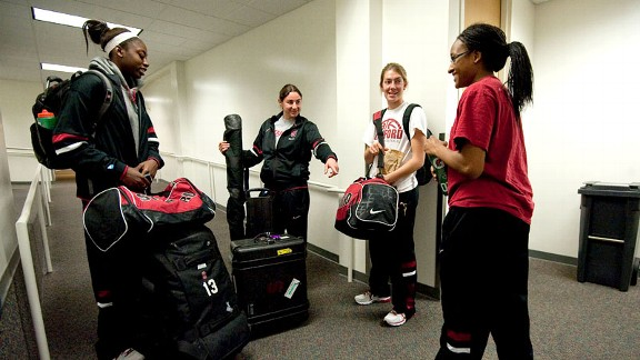 Video coordinator Lauren Greif, second from left, assigns freshman Alex Green, far right, to transport equipment before leaving the Stanford campus to play Texas in Austin. Freshmen players are responsible for equipment on each road trip.
