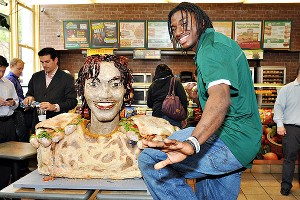 Robert Griffin III poses with his life-size smokehouse barbecue sandwich sculpture.