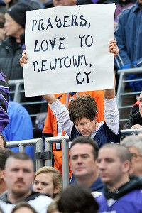 A fan in Baltimore holds a sign remembering the 26 victims of the elementary school shootings in Newtown, Conn. Moments of silence were held around NFL stadiums Sunday.