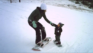 Abbie Berg with her daughter, June, on the snowboard Berg made just for her.