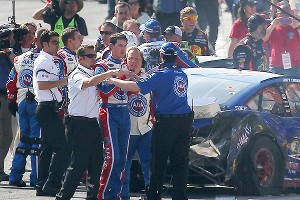 Joey Logano is held back by crew members after an altercation with Tony Stewart following the Sprint Cup race at Auto Club Speedway.