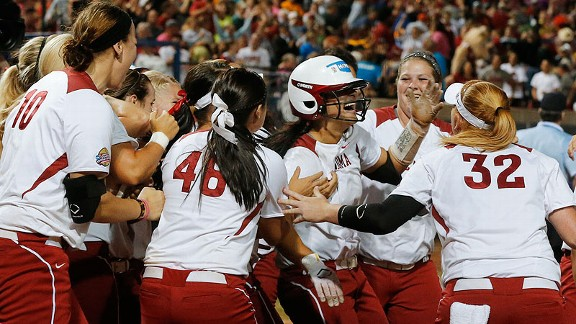 Lauren Chamberlain, center with batting helmet, gets mobbed by teammates after her 12th-inning walk-off home run lifted Oklahoma to a 1-0 lead in the WCWS on Monday night.