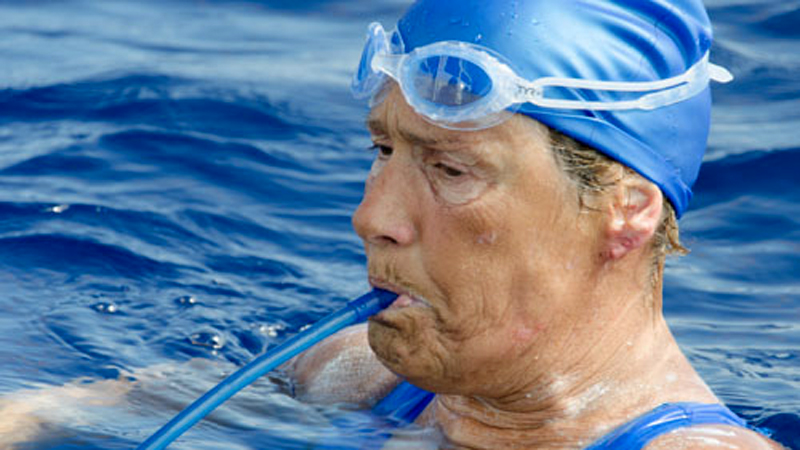Diana Nyad drinks from a tube hooked to a CamelBak hydration pack to get fresh water.