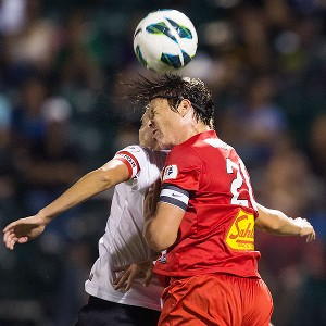 Abby Wambach of the Western New York Flash heads a ball against Portland Thorns FC's Christine Sinclair.