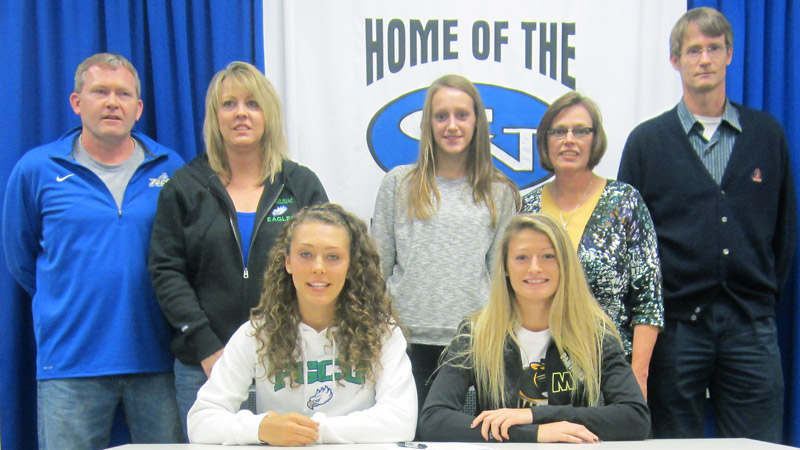 Columbus North (Ind.) stars Tayler Goodall, left, and Kelsey Cunningham were surrounded by family when they signed their national letters of intent on Wednesday. Goodall is headed to Florida Gulf Coast, and Cunningham signed with Wisconsin-Milwaukee. I(Photo Courtesy Columbus North athletics)/I