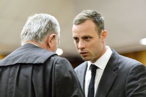 Oscar Pistorius, right, speaks with his lawyer Barry Roux before the start of his trial Monday in Pretoria, South Africa.