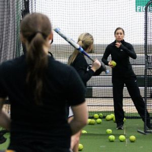 Former U.S. Olympian Lauren Lappin pitches batting practice to her Roosevelt players.