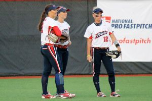 Suiting up with her last team, the USSSA Pride, Jessica Mendoza catches up in the outfield with teammates Caitlin Lowe and Kelly Kretschman.