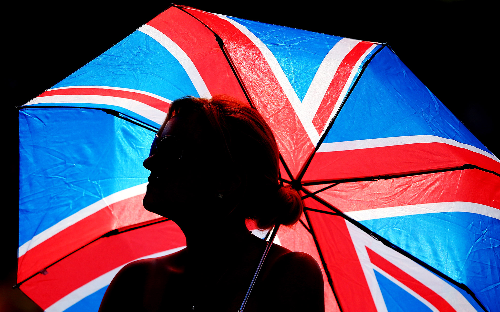 A fan gets shelters from the sun under a union jack umbrella on Day 9 of Wimbledon.