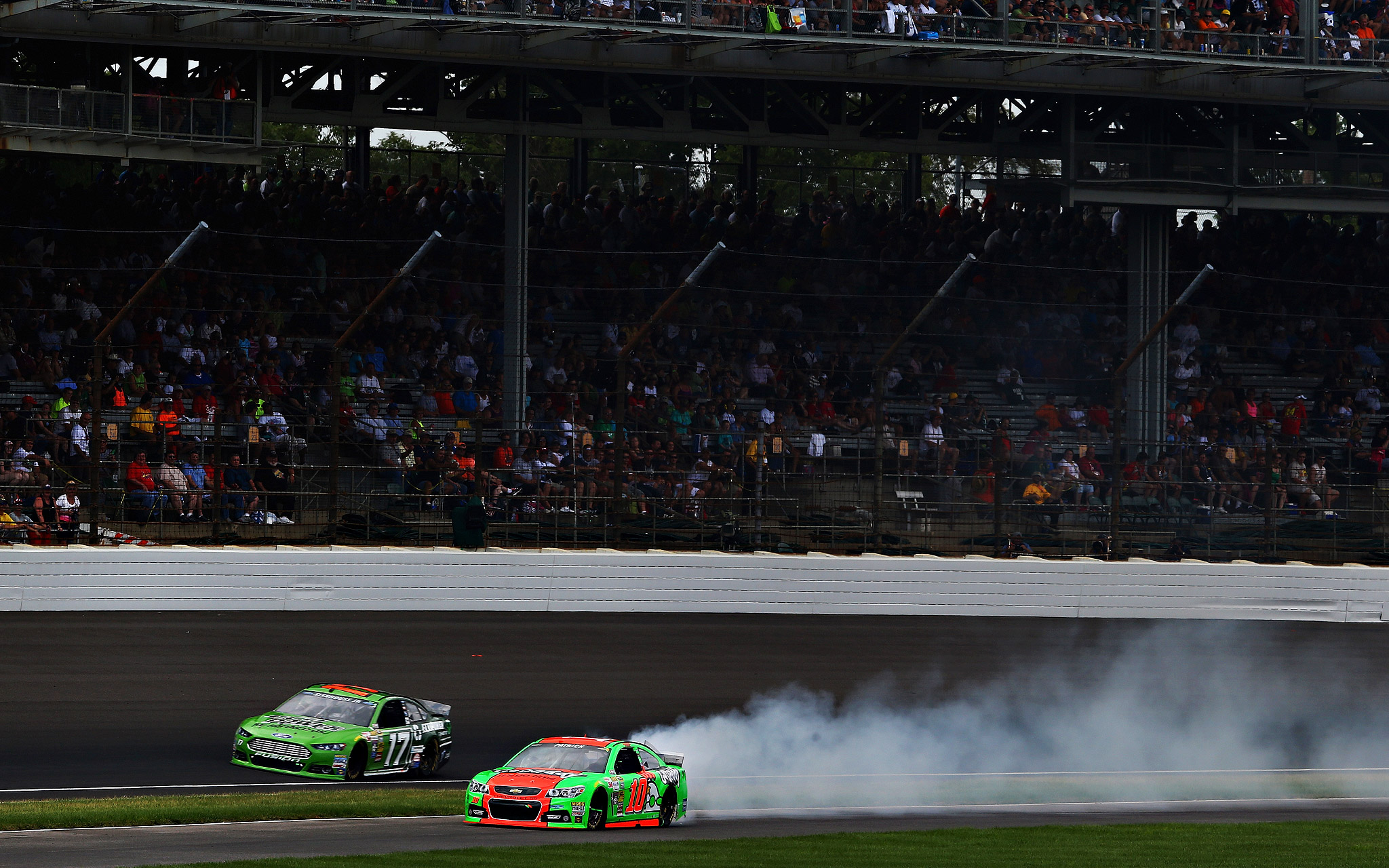 Smoke pours from the No. 10 GoDaddy Chevrolet, driven by Danica Patrick, on her way back to the pits during the NASCAR Sprint Cup Series Brickyard 400 in Indianapolis.