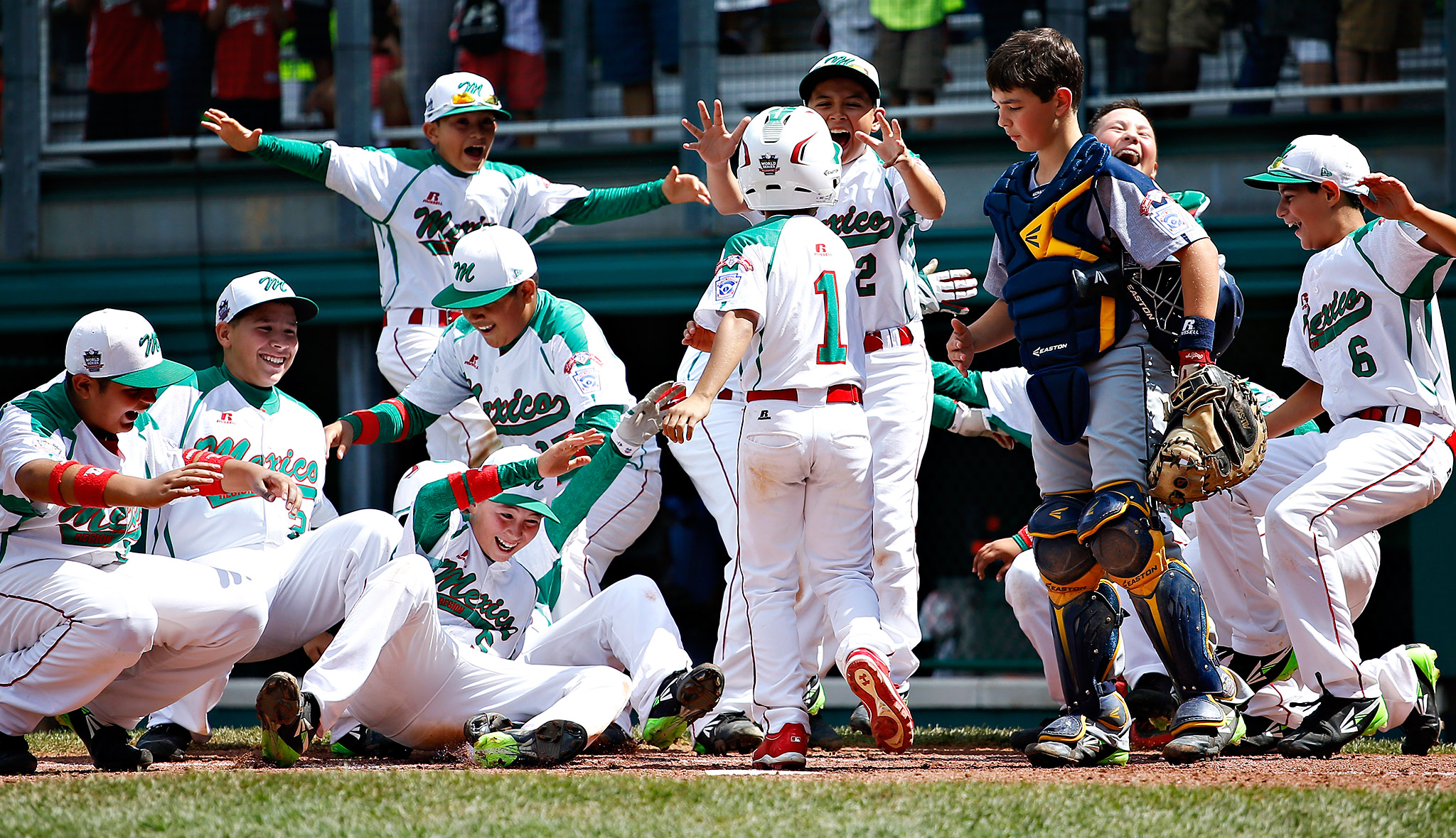 Mexico's Ruy Martinez, center, No. 1, got a hero's welcome from his teammates at home plate after homering against Australia.