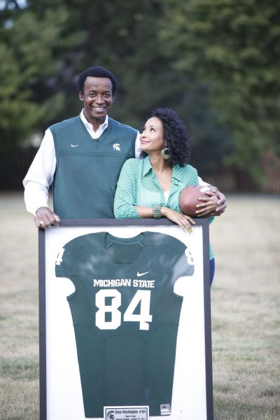 Father and daughter pose with Gene's No. 84 jersey on the Michigan State field.