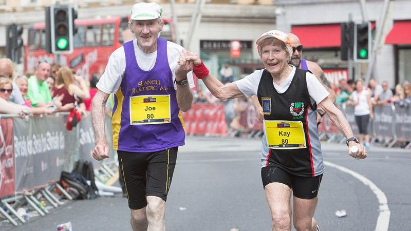 Kay and Joe O'Regan cross the 2016 Cork City Marathon finish line while holding hands.