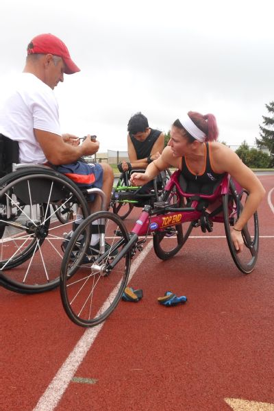 With the help of coach Adam Bleakney, Amanda McGrory removes a sticky bit of tape from the handrings on her racing chair during a recent Tuesday-morning workout.
