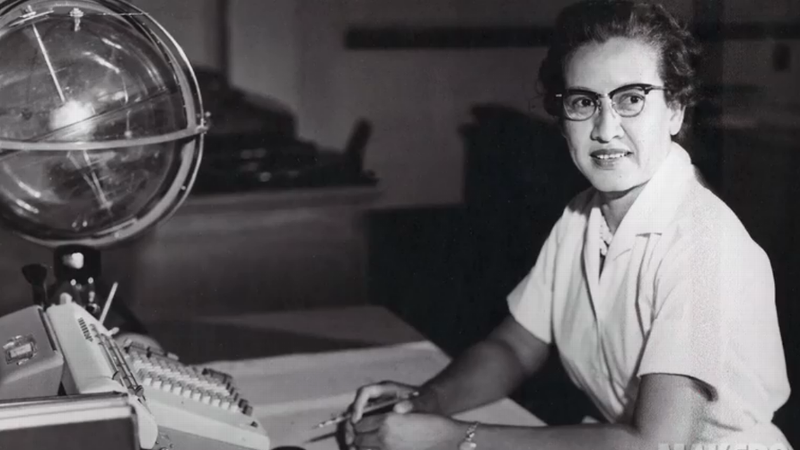 Katherine Johnson sits at her desk with a globe, or Celestial Training Device.