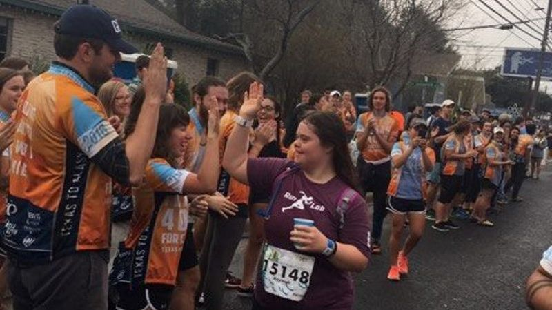 Kayleigh Williamson receives high-fives at a water stop during the Austin Half Marathon.