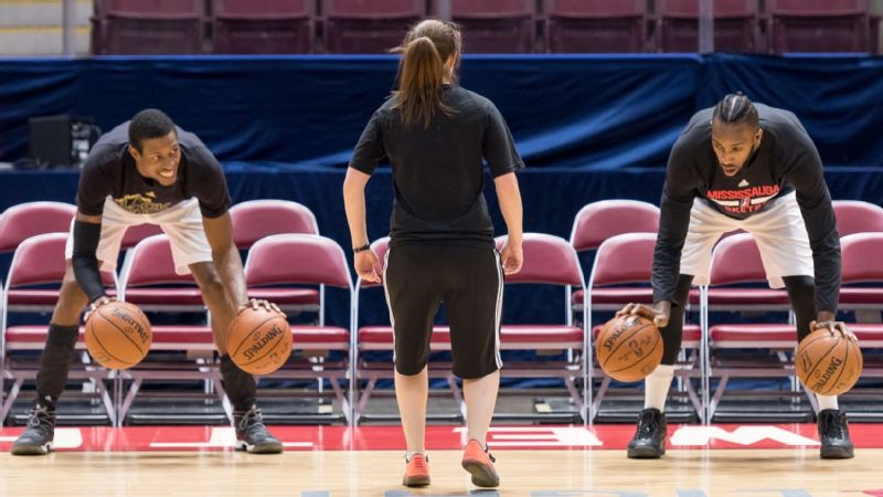 Nicki Gross, center, on the court with Raptors 905 players Antwaine Wiggins, left, and C.J. Leslie.