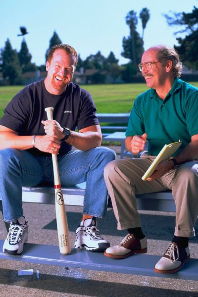 Kindred, right, has gone toe-to-toe with some of sports' biggest personalities throughout the years, including with then-baseball star Mark McGwire, pictured here in 1997.