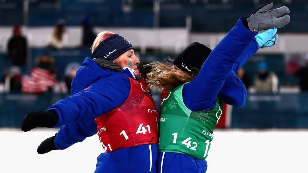 Kikkan Randall (left) and Jessie Diggins celebrate their cross-country team sprint success on the podium as they receive their gold medals.