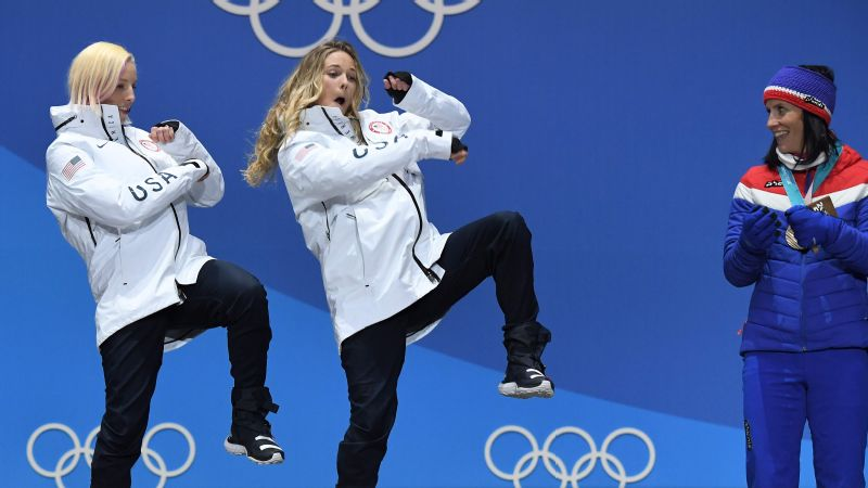 Olympic gold medalists Kikkan Randall and Jessie Diggins dance on the podium during the medal ceremony in Pyeongchang.