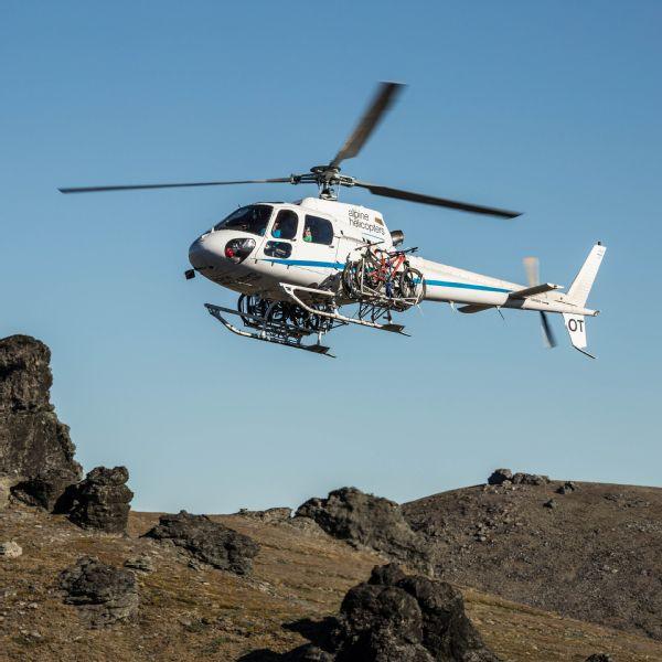 The helicopter transports the bikes to locations that would otherwise be inaccessible.